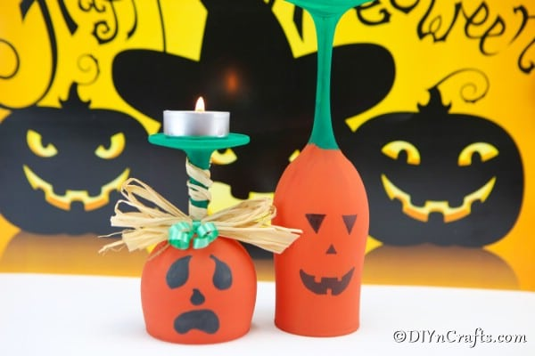 Two pumpkin art wine glasses sitting on a white surface with a yellow halloween themed background