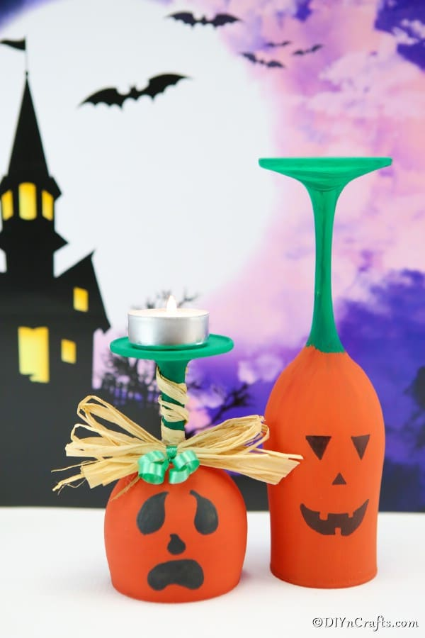 Two wine glass pumpkins sitting on a white surface with a purple halloween image in the background