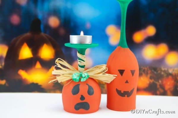 Up close picture of painted wine glass pumpkin art in front of blue halloween themed background