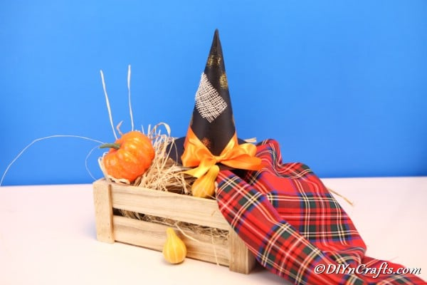 Witch hat sitting on a basket alongside mini pumpkins with blue background