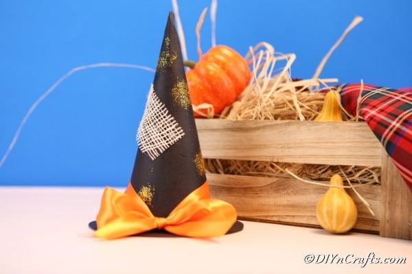 Witch hat sitting on counter in front of a wooden basket filled with hay and mini pumpkins