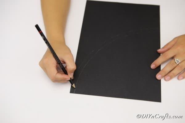 Tracing the curve on black cardboard for a witch hat