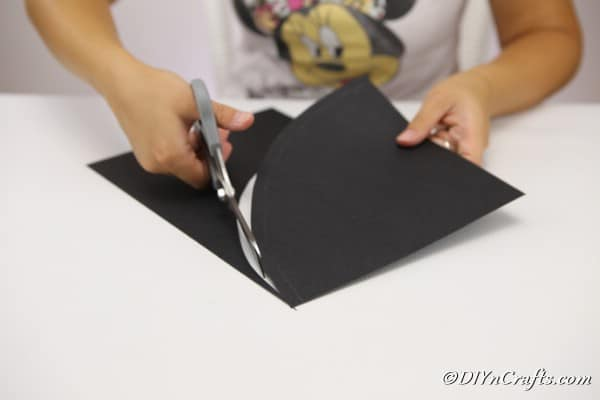 Cutting the cardboard into a curve for making a witch hat