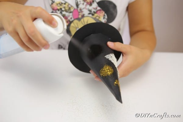 Spraying glitter onto the witch hat decoration