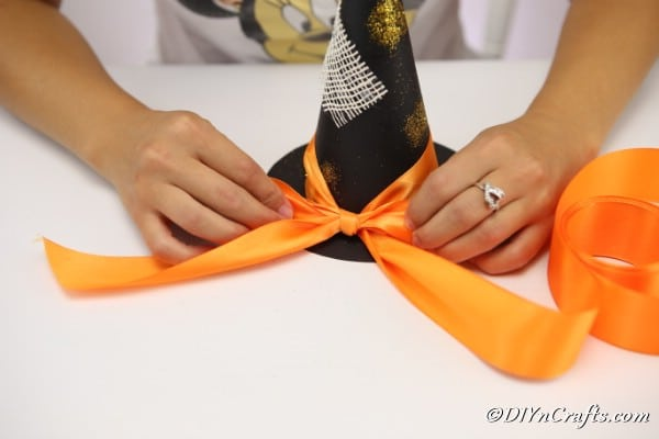 Tying ribbon onto the base of the witch hat decoration