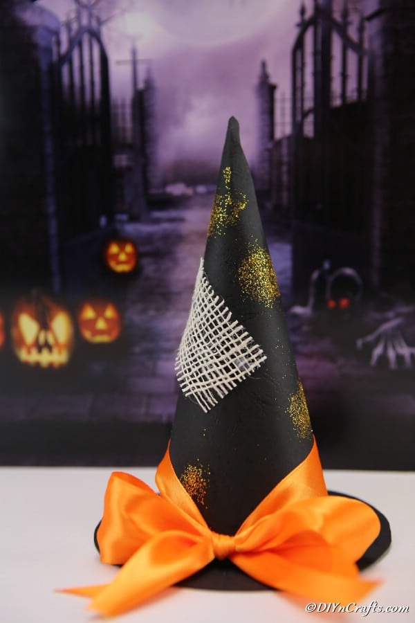 Witch hat sitting on white table with purple halloween banner behind