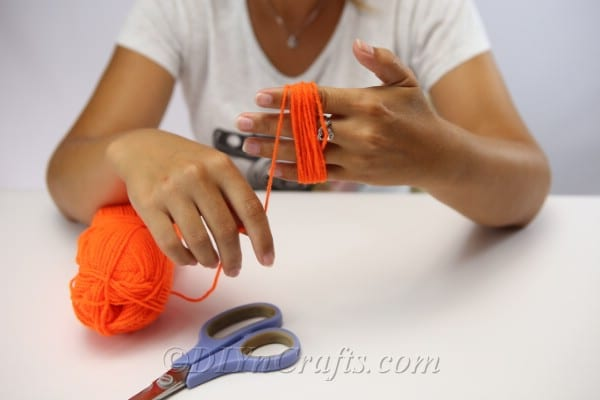 A woman making a circle of yarn around her hand to create a yarn pumpkin for the diy falll decor garland