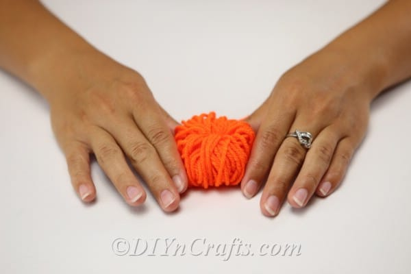 Fluffing yarn out to make the diy fall decor yarn pumpkin look like a pumpkin