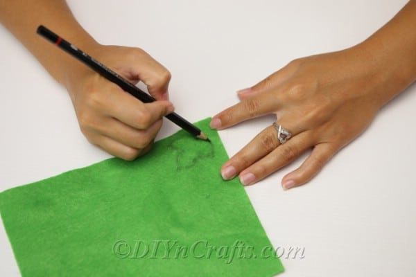 Drawing leaves on the green felt to create leaves for the yarn pumpkin that goes on the diy all decor garland