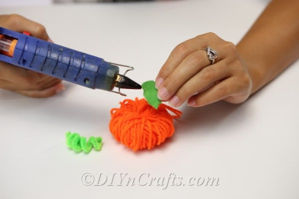 Attaching the felt leaf and pipe cleaner stem to the yarn pumpkin for the fall garland craft