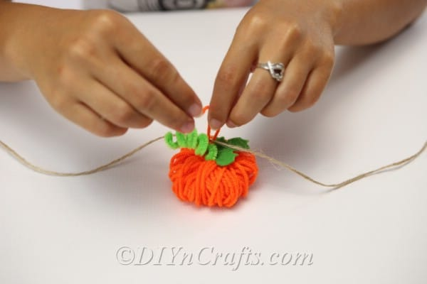 Tying the yarn pumpkin to the thread of the diy fall decor garland