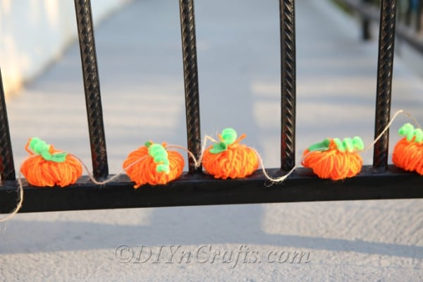 A DIY fall decor yarn pumpkin garland displayed outside on a black fence