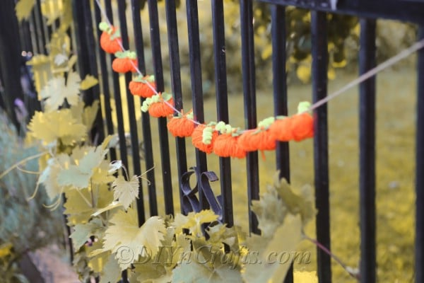 The diy fall decor yarn pumpkin garland hanging outside on a black metal fence