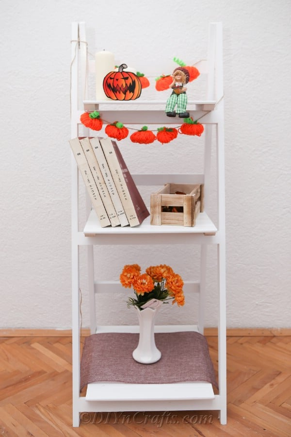 Yarn pumpkin garland displayed inside on a white shelf
