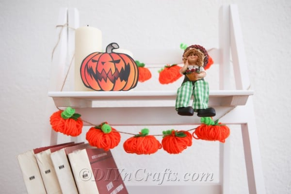 Yarn pumpkin garland diy fall decor hanging on a white shelf next to pumpkins and toy scarecrows
