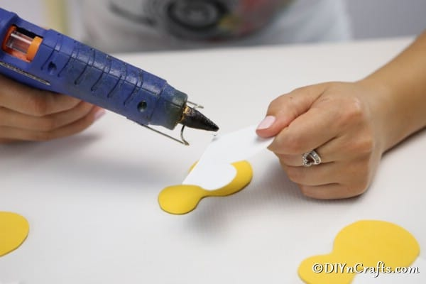 Gluing wings onto a yellow bee for bee decoration