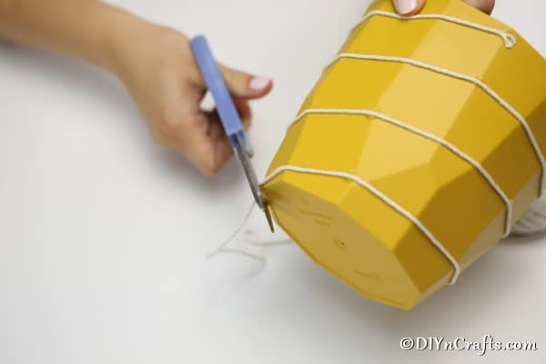 Finish attaching the white thread to outside of beehive bee decoration flower pot