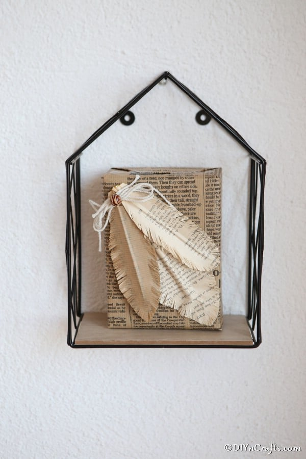 A black wire shelf hanging on a wall with a book that has paper decorative feathers attached