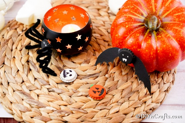 Fun magnets for Halloween sitting on a woven mat with candles in background