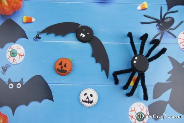 Fun magnets made to look like spiders pumpkins bats and ghosts on a blue background