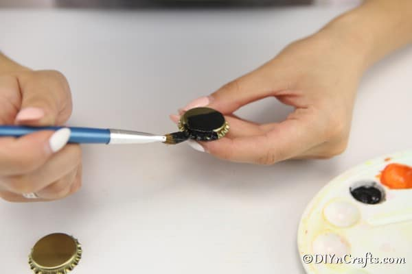 Painting a bottle cap black to create a spider magnet