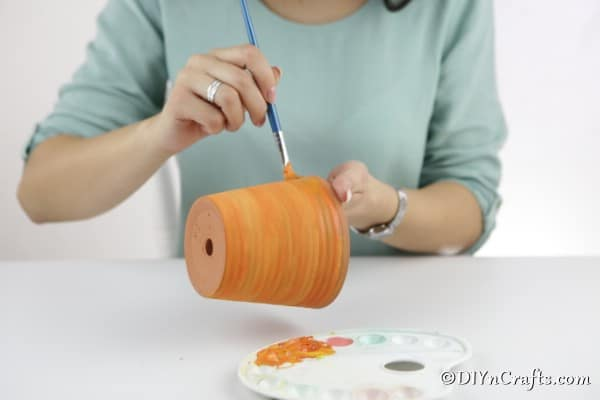 Painting the terra cotta paint for a pumpkin planter