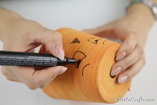 Drawing a face on the pumpkin planter with black paint pen