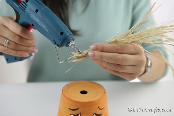 Gluing hay hair to top of clay pot pumpkin