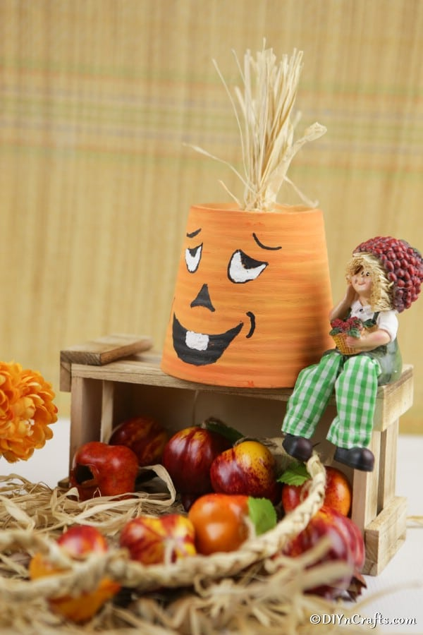 A terra cotta pumpkin planter sitting on top of a wooden box with other fall decor