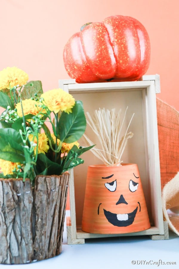 A pumpkin planter displayed in a wooden box