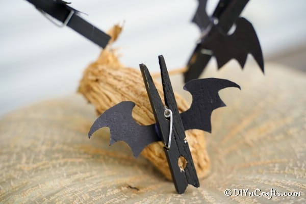 A clothespin bat sitting on top of a pumpkin