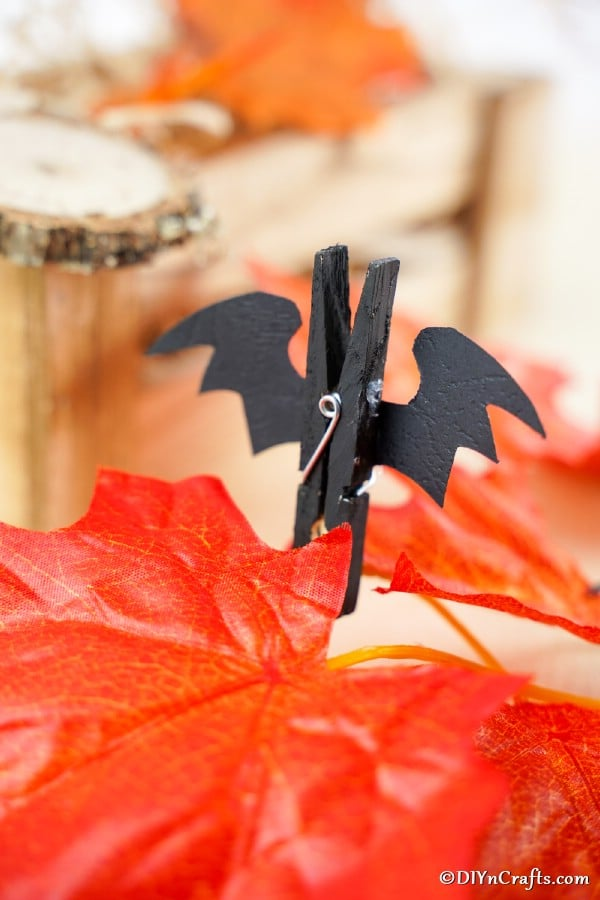 A halloween bat clothespin sitting on an orange artificial leaf