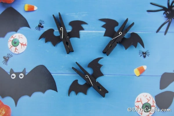 Completed Halloween bat clothespins on a blue background