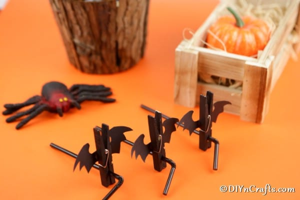 Halloween bat clothespins on straws sitting on an orange surface