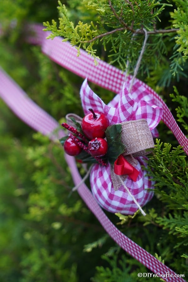 A checkered fabric homemade christmas tree ornament on a tree with red and white ribbon