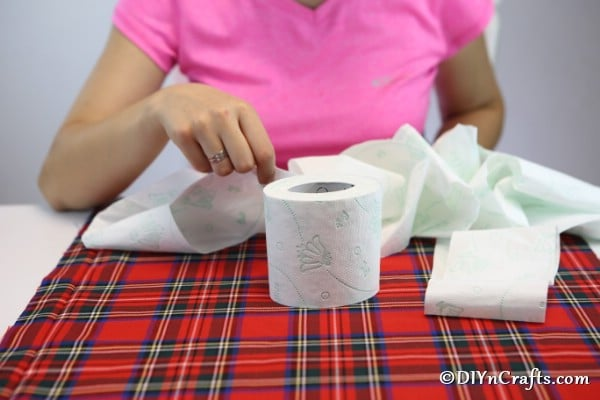 unwrapping a toilet paper roll to create pumpkin