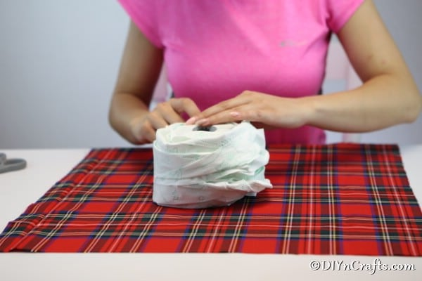 Rewrapping the toilet paper roll to make a fabric pumpkin shape