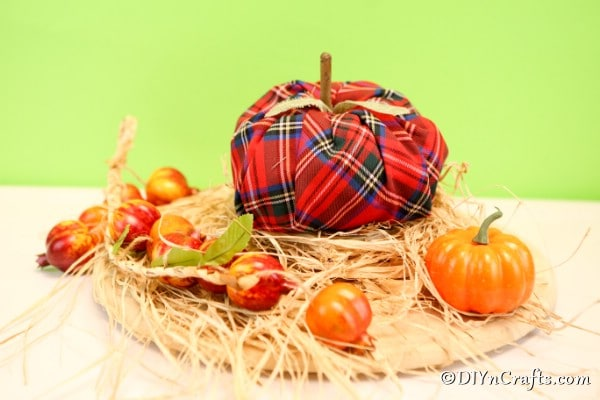 A fabric pumpkin sitting on straw surrounded by mini pumpkins in front of green background