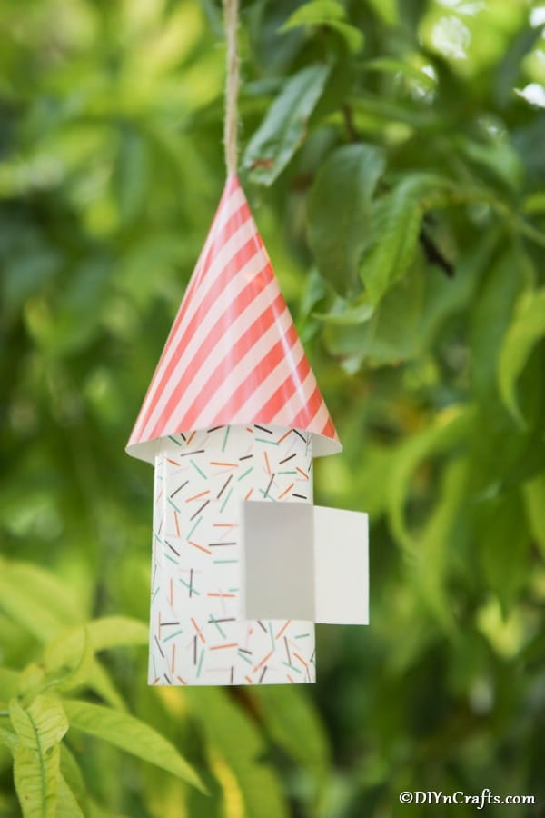 Up close picture of a striped gnome house hanging in a tree