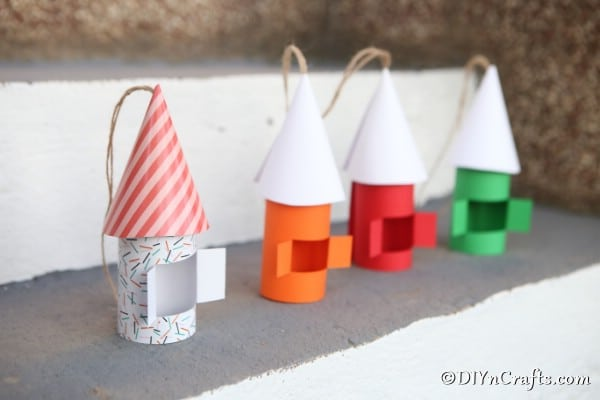 A line of gnome house in multiple colors on a concrete shelf