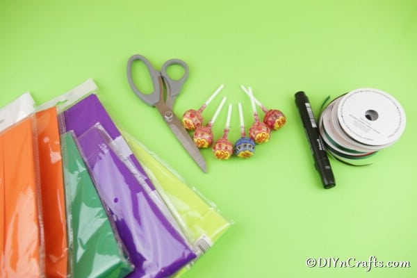 Supplies for making ghost lollipops on a green surface