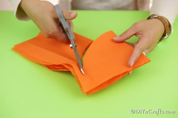 Cutting tissue paper into circles to create lollipop ghost crafts