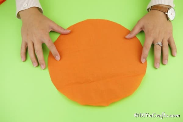 An orange circle of tissue paper laying on a green surface