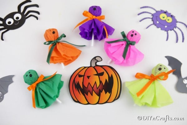 Halloween lollipop ghost craft treats laying on a white surface with spider and pumpkin stickers