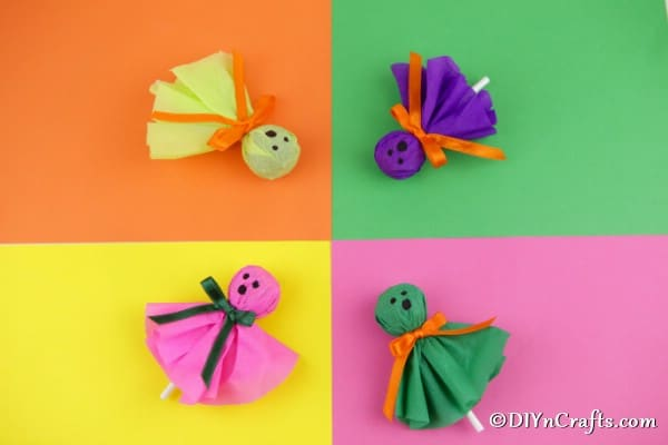 A variety of ghost lollipops laying on different colored papers