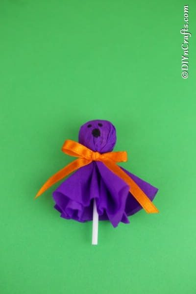 A purple ghost lollipop laying on a green surface
