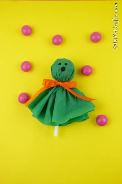 A green ghost craft lollipop on a yellow surface surrounded by pink gumballs