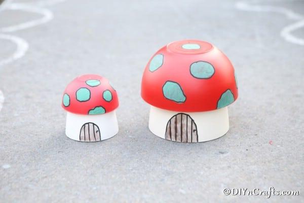 Two mushroom planter houses on a sidewalk