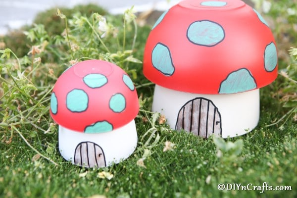 Two mushroom planter craft fairy houses on grass