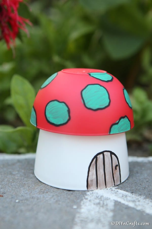 Up close picture of a mushroom planter fairy house garden decoration on a sidewalk near shrubbery
